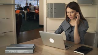 A woman is busy during the workday, she uses a laptop to solve client's tasks. She is talking by a cellphone in a single office