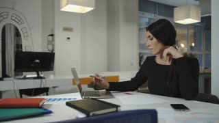 A woman working at the computer, taking notes on a sheet, crumples and throws. UHD