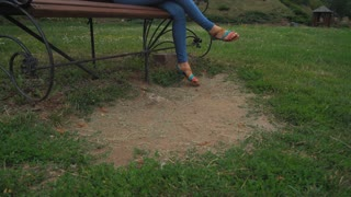 A young girl in a green jacket and jeans sits on a wooden bench in the park and swipe pages on your tablet