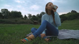 A young girl with brown hair sitting on the lawn in the park on blankets and drinking a glass of coffee. Laughing, rejoicing