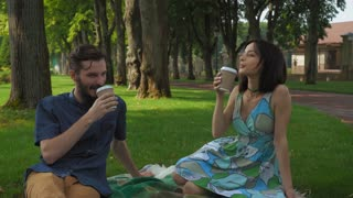 A young guy with a beard brunette girl talking and drinks coffee, sitting on the lawn in the park. Smile and enjoy a picnic and date