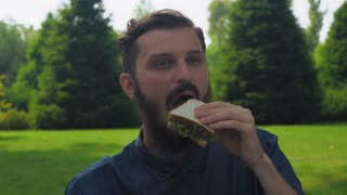 A young guy with a beard in a blue shirt eating a sandwich with salad in the park. Enjoying the taste