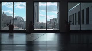 A young man in a light shirt goes down a long corridor of office space with high windows in which dark, casually and looking out the window at passersby