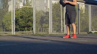 Adult caucasian man dribbling ball on the basketball court outdoors. young sportsman play alone on the street. Male trains sport skills in the morning in summer season. guy wearing in casual t-shirt