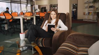 Adult woman at the office using touch screen tablet for watching photo from vacation.  Business woman smile and  laugh. Female with long red hair rest at work after hard project  she drinking coffee