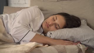 Adult woman sleeping in bed in bedroom. waking up with happy smile on her young face. Attractive lady wearing in white sleepwear her shine brown hair lying on pillow. blissful morning at home