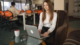 Adult woman with brown hair typing on computer. She finish her work and relax at the chair. Female smile and  satisfied her business project.Business woman dressed in white shirt and black trousers