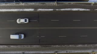 Aerial - Cars driving on a two-lane road through a snowy landscape. 4k video