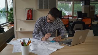Architect checking details and make notes on the paper plan. Documents and computer on the wooden table with equipment for drawing and draftsmanship. Male wearing in casual clothes work in modern