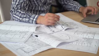 architect working with architectural document. Man hands holding pencil check blueprint sketch make notes at the working place. On the wooden desk laptop. Wearing in casual shirt