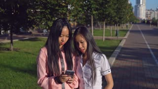 Asian friends looking on the screen smartphone choose item in online shop. Young women talking in the city. Woman holding mobile phone using internet for shopping on the street. Happy girls smiling