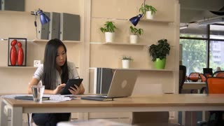 Asian woman reading documents on touch screen tablet. Business woman working in modern office