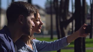 Attractive couple friends take selfie photo in the city. Adult man and woman have fun in city. Girl showing tongue guy holding smartphone people laughing