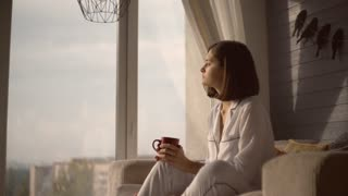 Attractive girl looks out the window at cosy flat. Portrait woman sitting near the big window holding red mug. Lady wearing in white pajamas sits in chair looking on the street and thinking