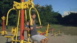 Attractive man doing workout for build bigger arms on the exercise machine at the outdoor gym. A young mixed race guy in a shirt and shorts athletic trained in specialized simulator in the park