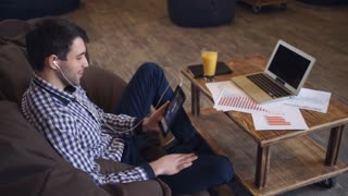 Attractive man holding tablet in hand, headphones dressed, online conference