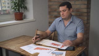 Attractive middle-aged man lays graphics and tables on the table
