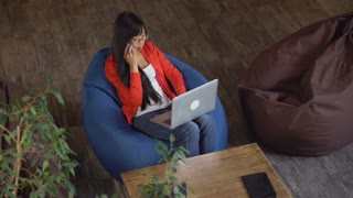Attractive student sitting in lounge room campus on the bag chair. Vietnamese woman chatting online using wifi. Female with long black hair and happy smile spend free time use internet. Multicultural