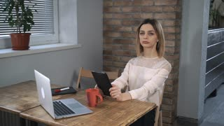 Attractive woman making a video call by tablet