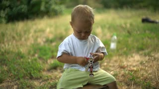 Baby with smile sitting in the park with green grass and trees. Happy boy child playing with keys. Beautiful caucasian kid wearing in t-shirt and shorts. Infant looking at the camera and laughing
