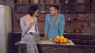 Beautiful couple in love enjoy morning in apartment. Young family drinking orange juice on breakfast. Attractive lady speaking with handsome man in kitchen. Two people talking discussing plans for day