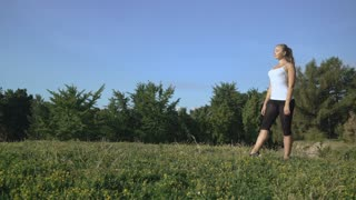Blonde girl in a white T-shirt makes an acrobatic trick wheel back and forth on the hill of green grass with a stop at top