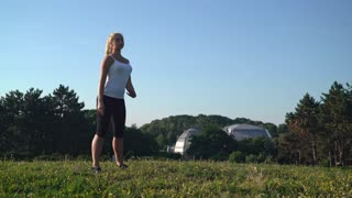 Blonde young woman doing workout for stretching body. Happy active lady trainings at the open air with beautiful summer nature