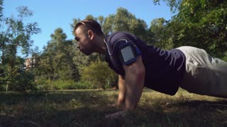 bodybuilder trains in park with green grass and trees. Caucasian adult man push-up outdoors