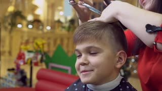 boy six year old in barbershop. Smiling little client sitting in the chair brunette hairdressser cutting hair. Young woman at the working place cuts hair cute kid