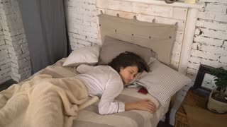 Brunette using smartphone and continued to sleep. Young woman sleeping in bedroom. Attractive lady wearing in sleepwear hiding the phone under the pillow. Adult girl lying in bed wearing in white