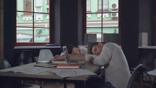 Business team young woman and adult man sleeping at the working place in modern office. Businessman and businesswoman lying on the desk and take a nap after hard project. workaholics in start up