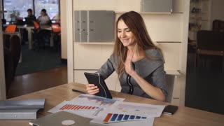 Business woman using app on the touch screen tablet. On her desk documets and charts with sales report
