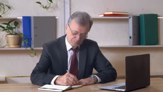 Businessman with silver hair writing notes in notebook. Elderly chief sitting at the working place in casual office and handwriting. Grey headed entrepreneur wearing in elegant suit. On the wooden