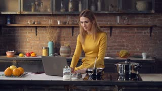 Businesswoman cooking dinner and working with laptop in the kitchen. Busy woman looking on the pc screen mixing sauce sitting near cooker. Caucasian adult model using internet in loft apartment