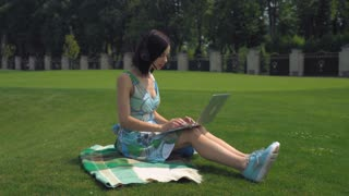 Businesswoman sitting on the lawn working on computer. Happy young professional woman surfing internet chatting with clients or has online video call with partner in the park. Female works remote on
