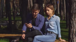 Busy man using smartphone on a date near sitting upset woman. Young people spend boring weekend in park