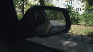 Car rides on the street in summer season with green trees on the sidewalk. We can see road and sign crosswalk and building in the wing mirror, also known as the fender, door or side view mirrors