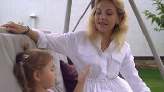 caring mother plays with little girl. Caucasian family with blond hair spend weekends in countryside. Woman wearing in elegant white shirt