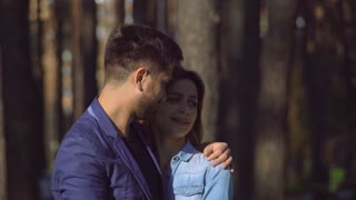 Caucasian cute family. Man and woman talking in the park in the early morning. Happy pair hug and speak on a date. Couple in love enjoy relationship spend time together in the city. Girl wearing in