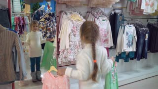 Caucasian girl standing near mirror choose clothes. Happy customer try on different dress