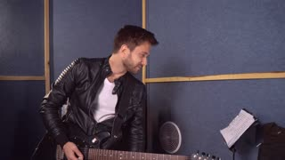 Caucasian guitarist with beard playing on the guitar in sound recording studio. Happy stylish guy wearing in leather jacket and skinny jeans white t-shirt. Man enjoy plays in the sound record studio