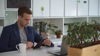 Caucasian man sitting at the contemporary office wearing in blue jacket and grey t-shirt. Professional young male drinking coffee from white mug. Guy looks like manager or ceo works in own office