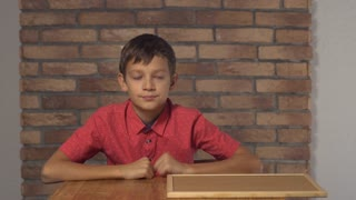 child sitting at the desk holding flipchart with lettering where on the background red brick wall. Schoolboy with asking on his face. Preadolescent wearing in casual red shirt