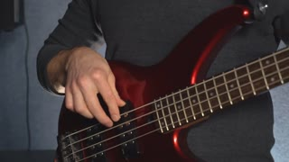 close up details man hands playing on red guitar. Male holding musician instrument wearing in grey sweater indoor