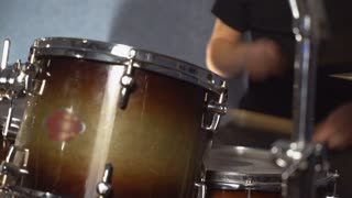 Close up drummer play on drum set. unrecognizable man wearing in casual jeans with hole and black t shirt. Detail pop or rock band in concert