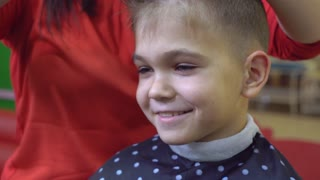 Close up portrait caucasian little boy in barbershop. Happy smiling kid sitting on chair in hairdressing salon