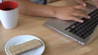Close up working place with laptop mug with tea and healthy cereal snack