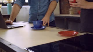 closeup details man and woman standing near table. On the desk red and blue cups. Man hands using laptop