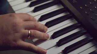 Closeup details man hands playing on piano. On guy finger wedding ring