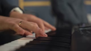 Closeup details man playing on synthesizer. married keyboardist hands with wedding ring